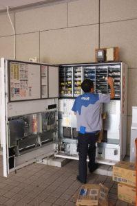 """Japanese worker changing vending machine beverages (9173452138)"" by Leonardo Boiko - Japanese worker changing vending machine beverages. Licensed under CC BY 2.0 via Wikimedia Commons -"