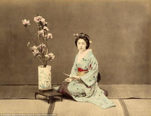 A geisha poses for a post card. Hard-tinted.